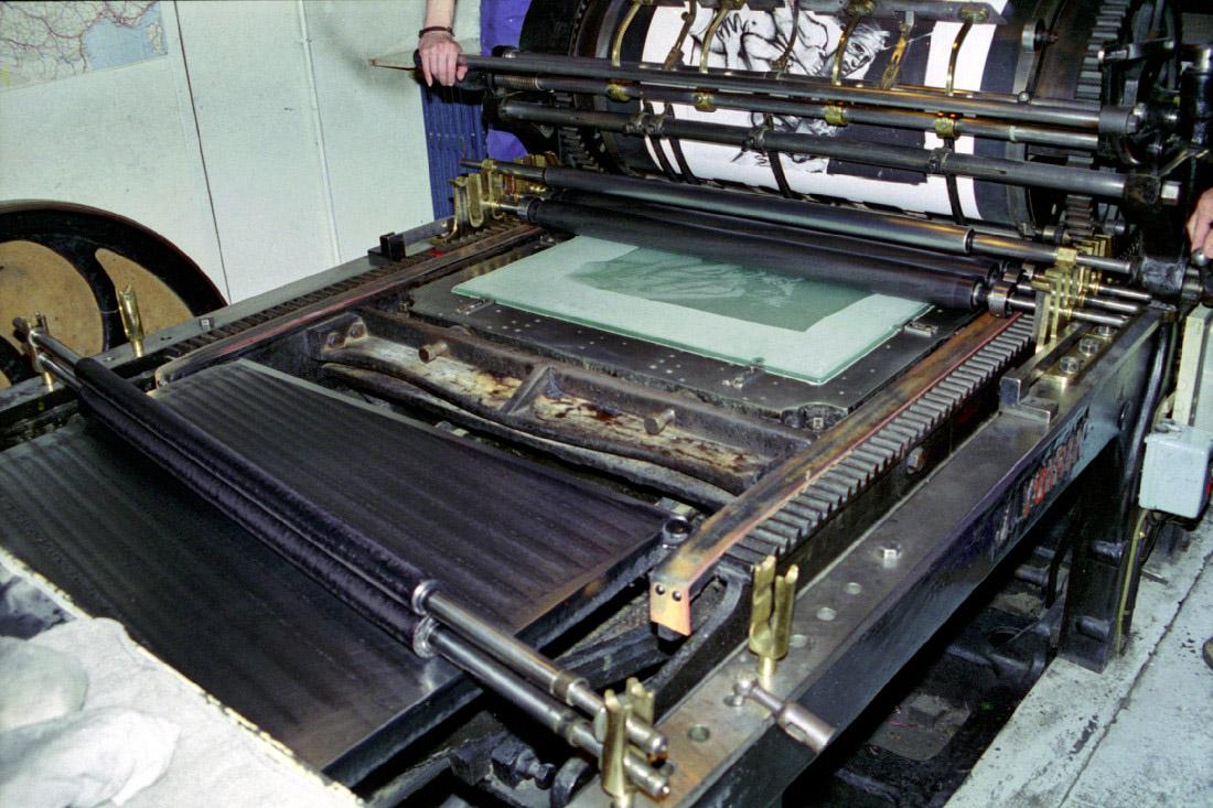 Photo Presse phototypie pendant le tirage des épreuves. La matrice d'impression passe sous le cylindre