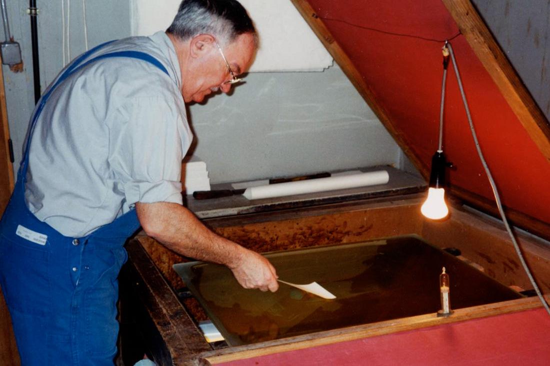 Photo la gélatine bichromatée est étalée à l'aide d'une feuille de papier